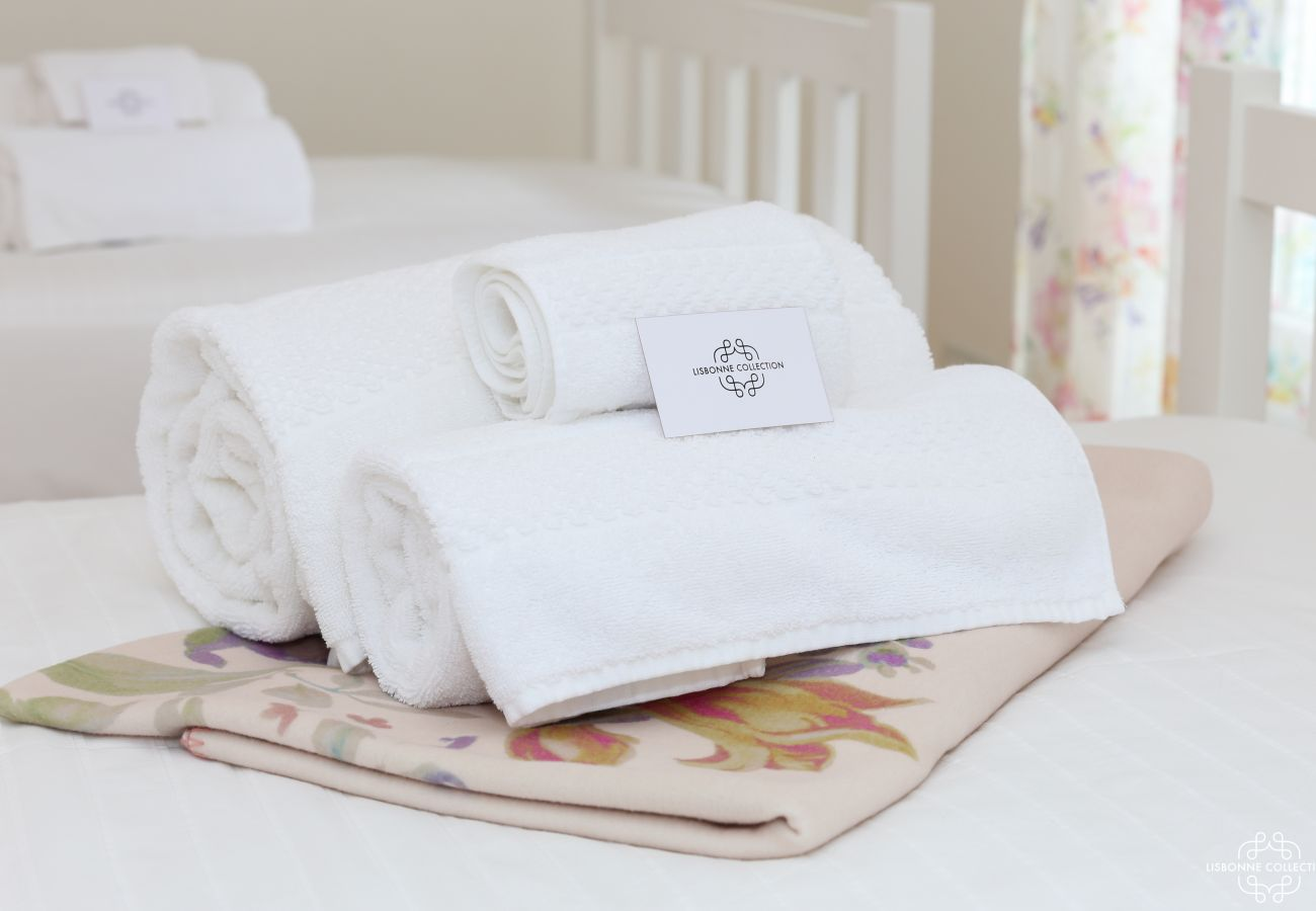 Bath towel folded and laid on the bed with carton