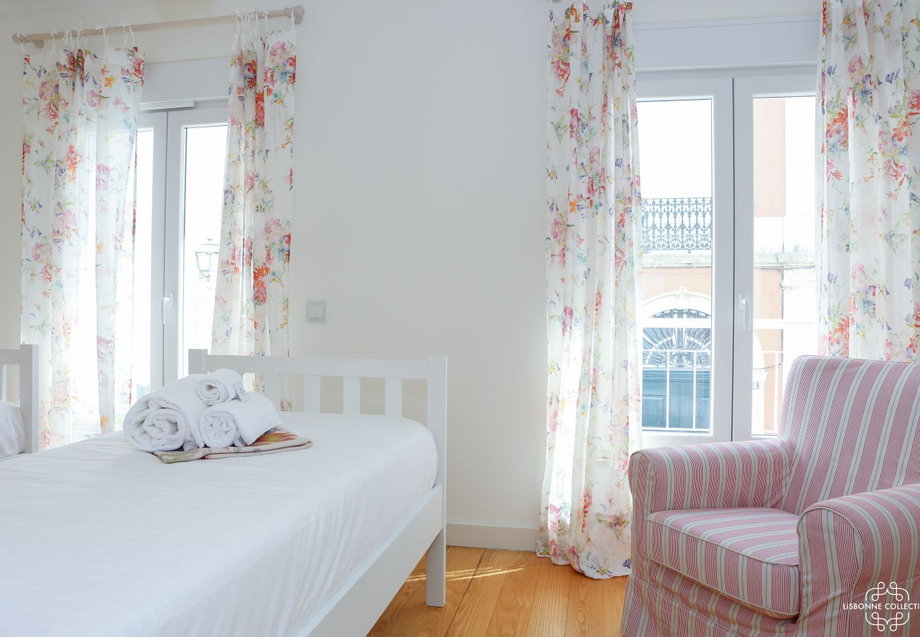 Bright room with two single beds, a single sofa and access to the balcony