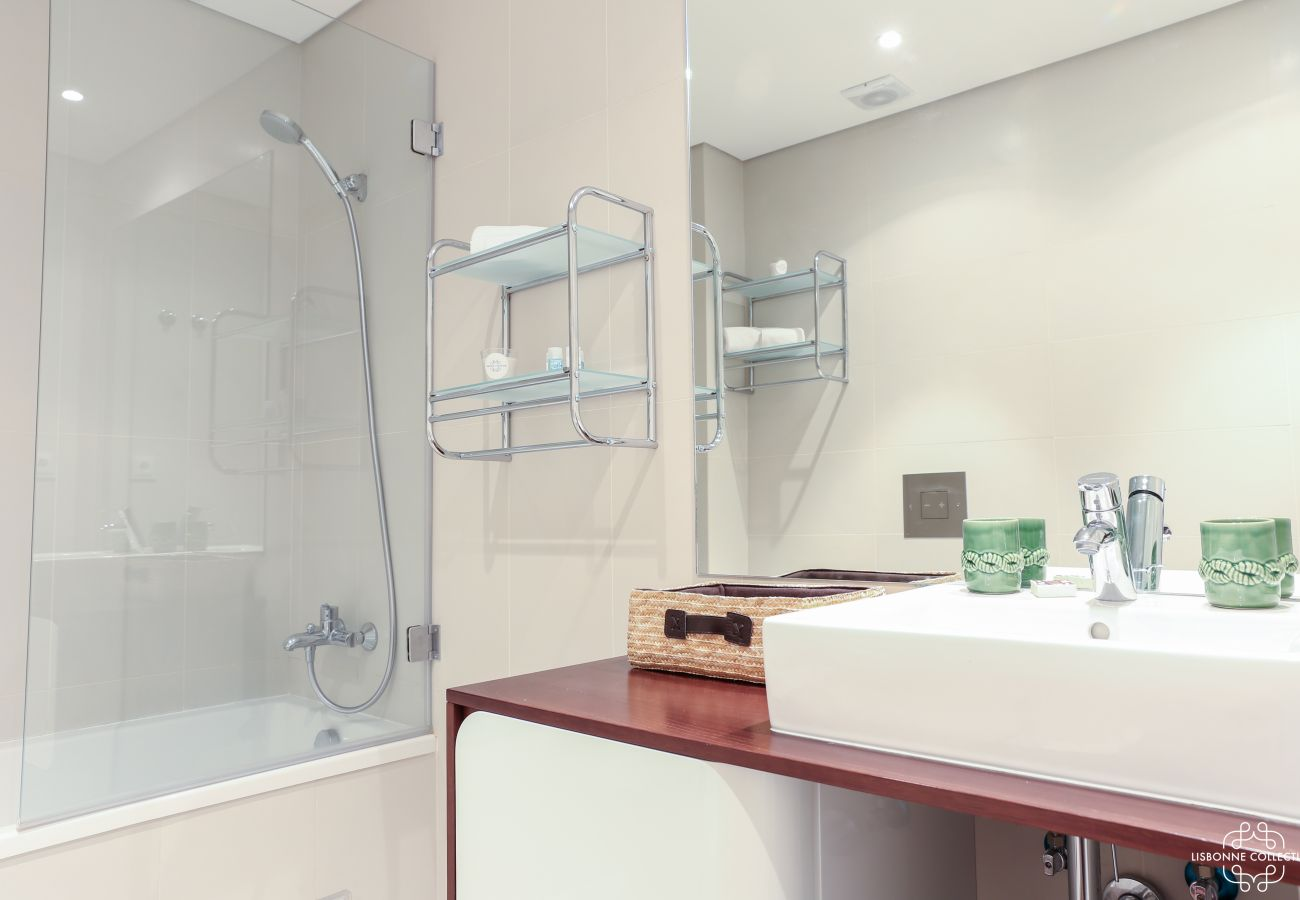 Modern bathroom with ceramic tub and vanity and wooden furniture