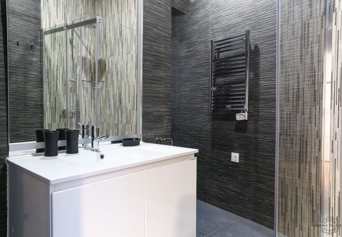 spacious and modern shower with basin, toilet and radiator and heated towel rail