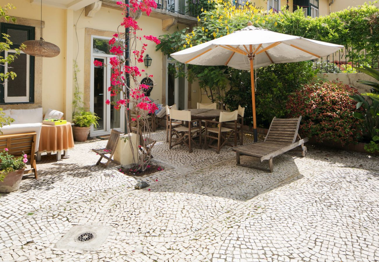 typical and warm garden in the center of Lisbon with table and chairs