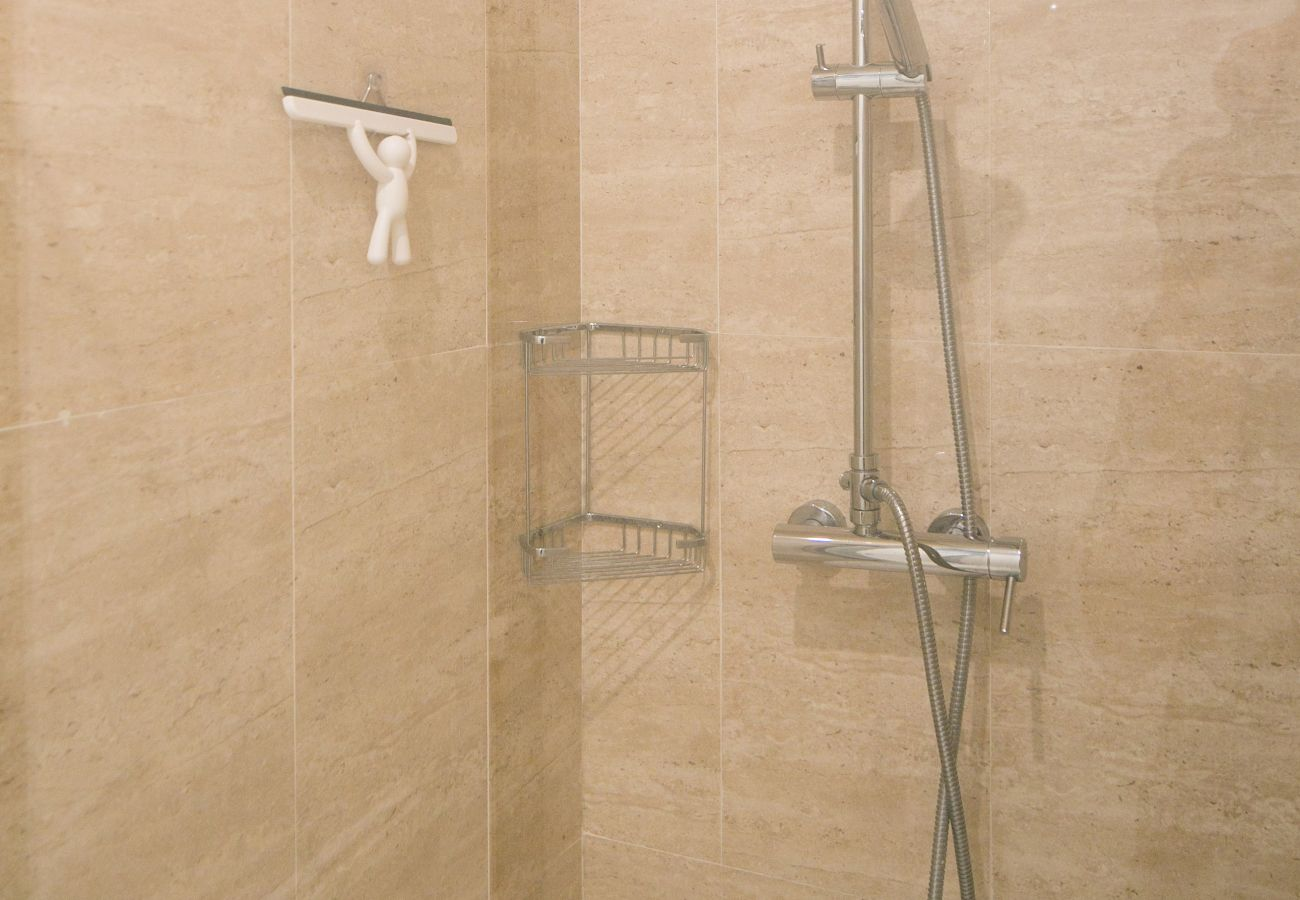 Spacious and modern shower with basin, toilet and towel radiator