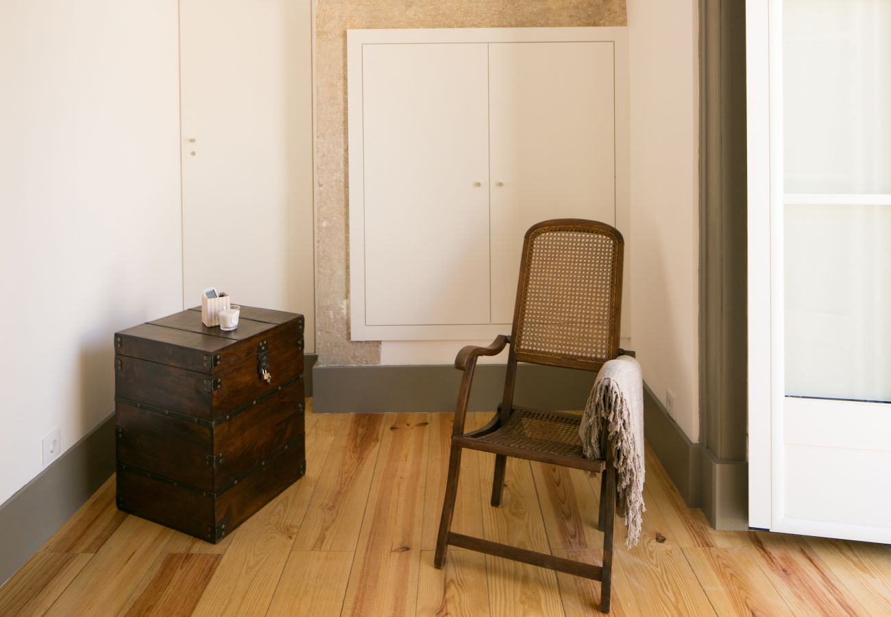 Decoration with rustic chair and wooden bedside table in front of a window