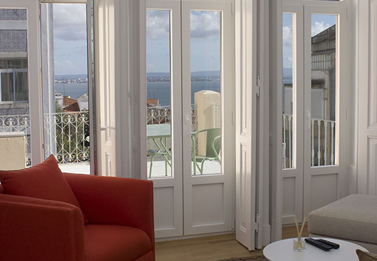French window leading to a large terrace with a beautiful view of the Tagus