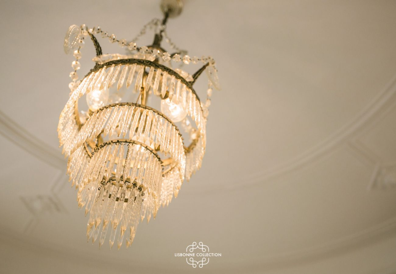 Crystal chandelier hanging on a typical Lisbon-style ceiling