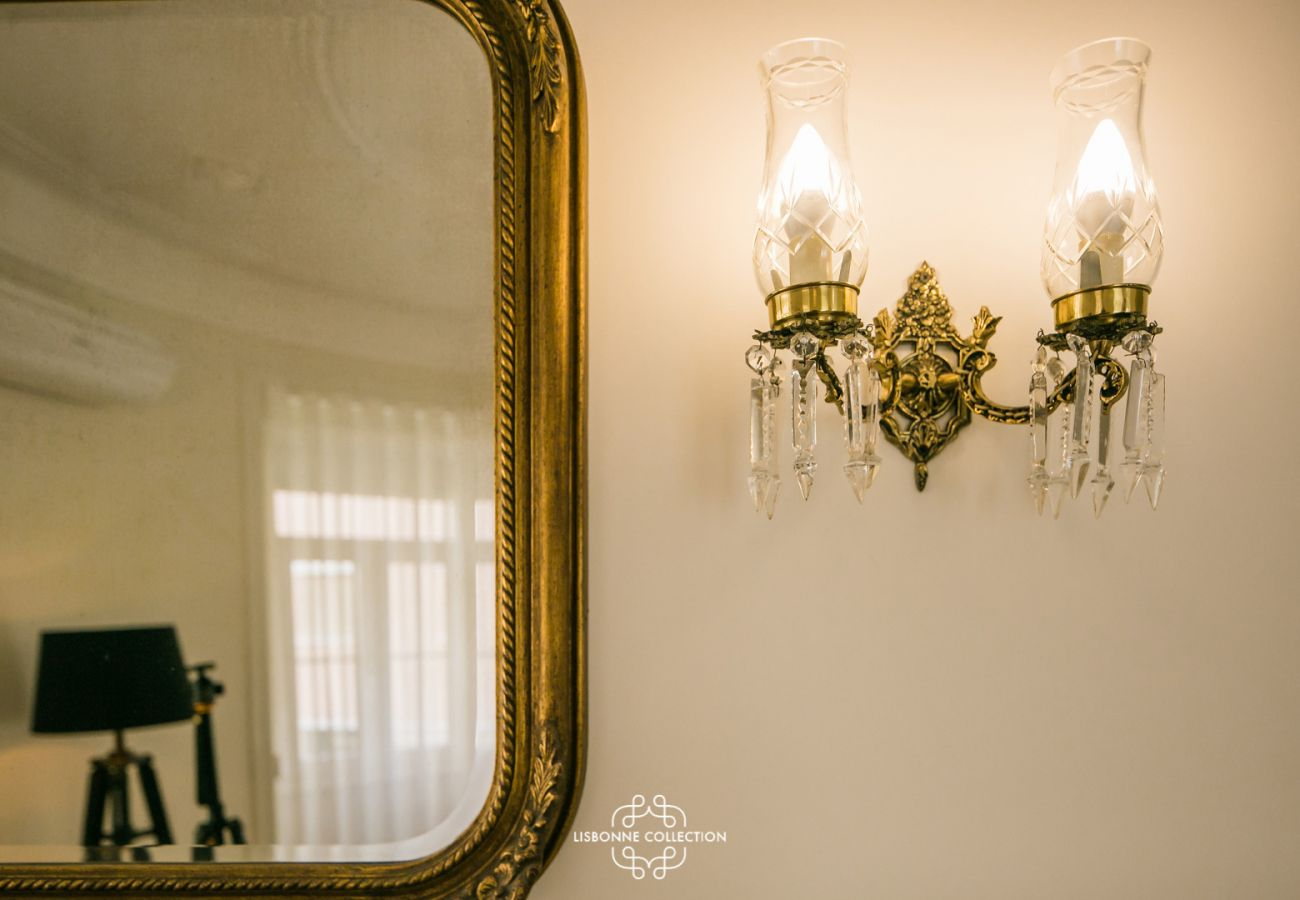 old mirror next to a small crystal lamp