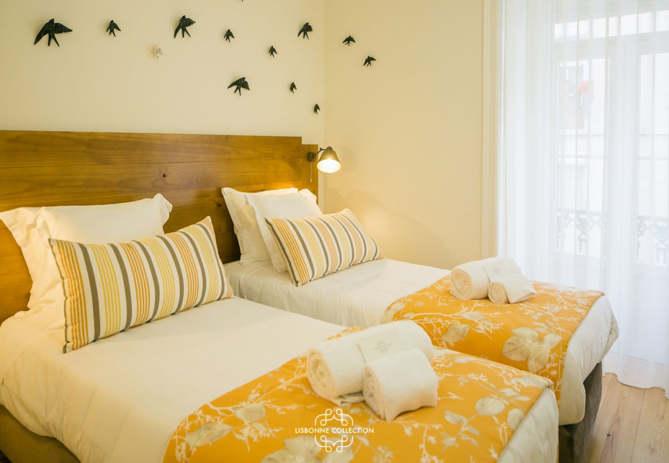 2 single beds with yellow plaid and swallows on the wall