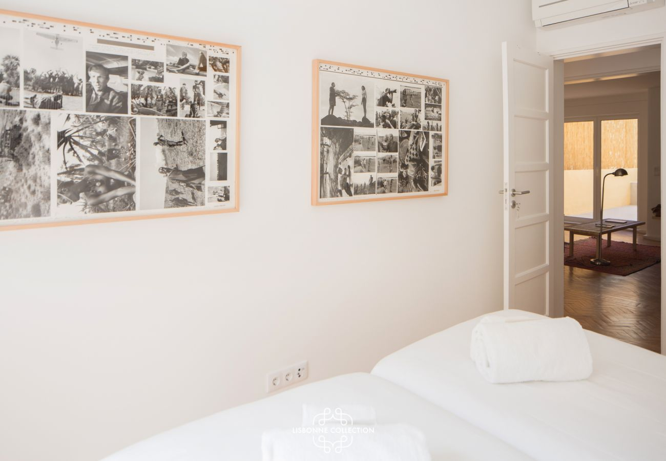 Bedroom with two single beds with historic pictures on the walls