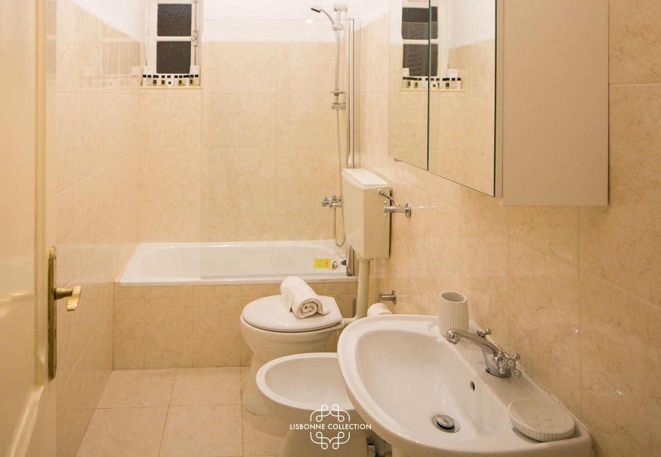 beige bathroom with large bathtub, bidet and washbasin