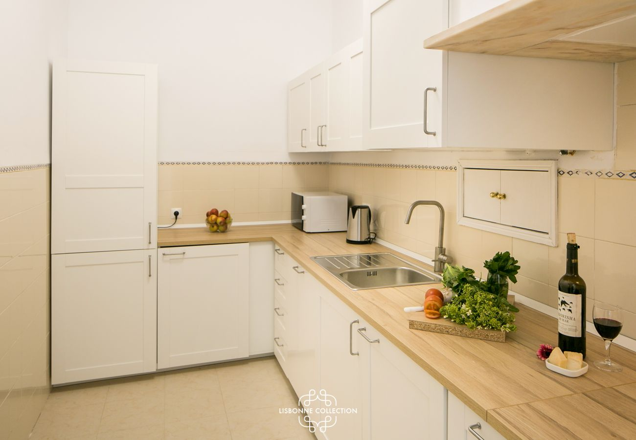 large bright kitchen with wooden worktop and bottle of wine
