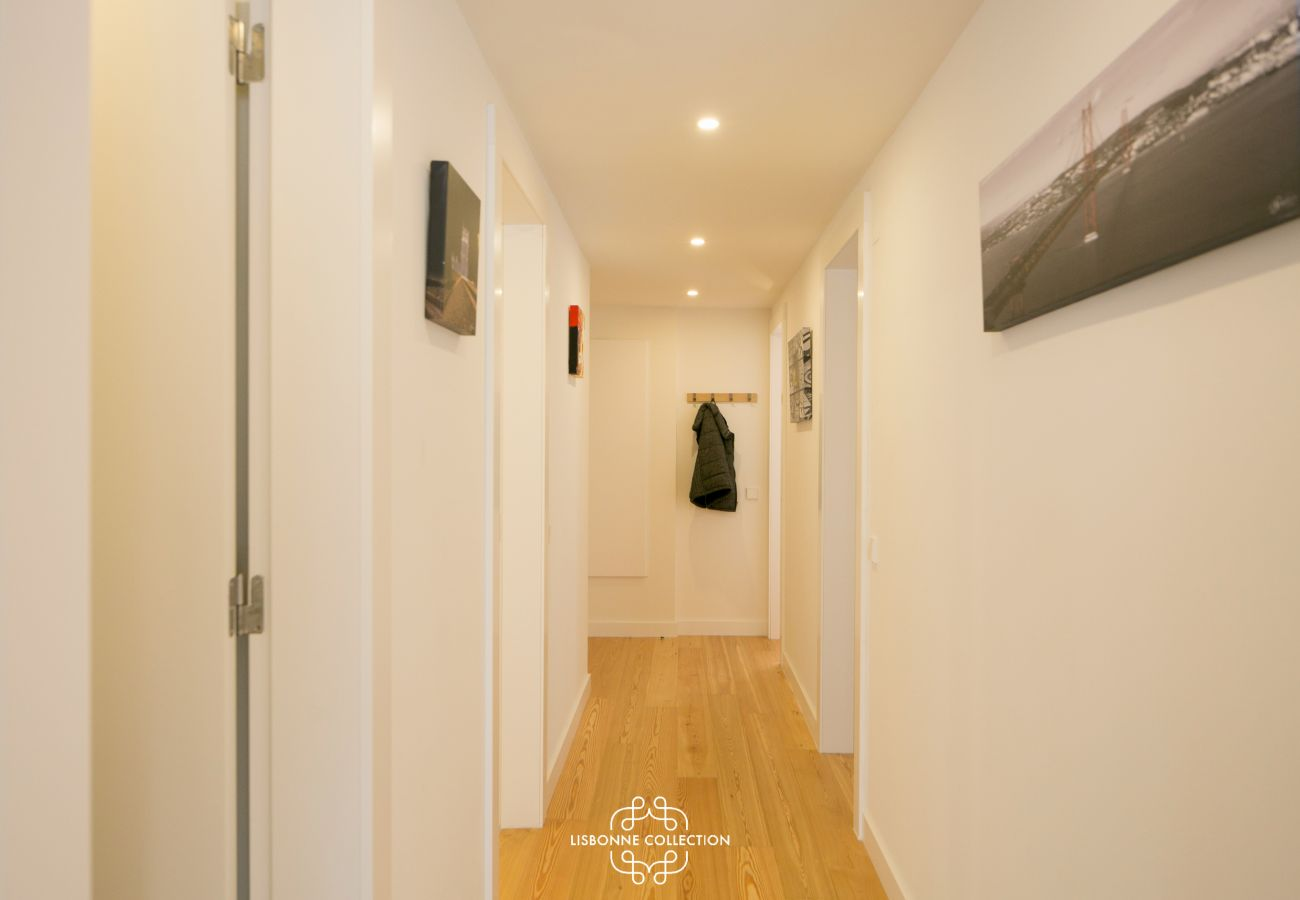 large hallway with white walls and doors and wooden floor