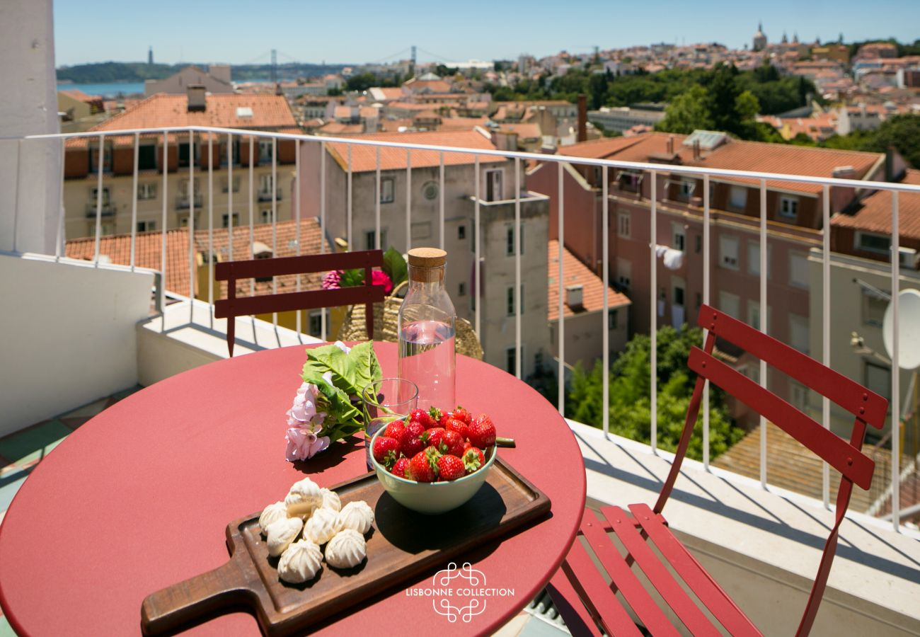 furnished terrace with red furniture and wide panorama of Lisbon